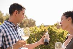 Человек и женщина говоря над бутылкой вина Стоковое Изображение