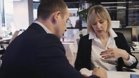 Человек и женщина говоря, обсуждающ в конференц-зале акции видеоматериалы
