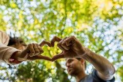 Человек и женщина делая, который делят сердце показывать Стоковые Изображения