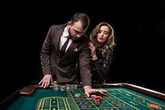 Человек и женщина играя на таблице рулетки в казино стоковые фото