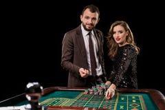 Человек и женщина играя на таблице рулетки в казино стоковое изображение rf