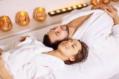 Человек и женщина лежа вниз на кроватях массажа на роскошном центре курорта и здоровья Стоковые Фото