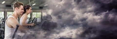 Человек и женщина на перекрестных тренерах с бурным облаком переводят Стоковое Изображение