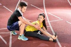 Человек и женщина на следе гари арены спорт протягивая тренировки Стоковые Изображения