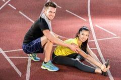 Человек и женщина на следе гари арены спорт протягивая тренировки Стоковая Фотография RF