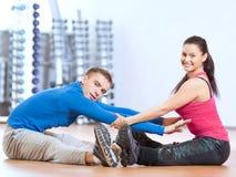 Человек и женщина на спортзале делая протягивать Стоковая Фотография