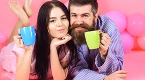 Человек и женщина на усмехаясь положении сторон, розовой предпосылке Пары ослабляют в утре с кофе Пары в кофе питья влюбленности  Стоковые Фото