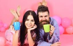 Человек и женщина на усмехаясь положении сторон, розовой предпосылке Пары в кофе питья влюбленности в кровати Концепция традиции  Стоковые Изображения