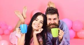 Человек и женщина на усмехаясь положении сторон, розовой предпосылке Пары в кофе питья влюбленности в кровати Пары ослабляют в ут Стоковая Фотография