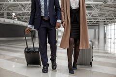 Человек и женщина носят их чемоданы Стоковые Фото