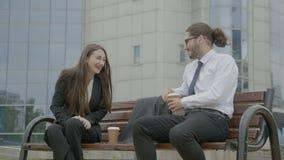 Человек и женщина нося официально костюм сидя перед корпоративным зданием на стенде и смеясь над и говоря в перерыве на чашку коф сток-видео