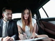 Человек и женщина обсуждая документы работы в такси Стоковое Изображение RF