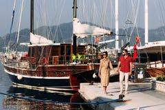 Человек и женщина около яхт на доке стоковые изображения rf