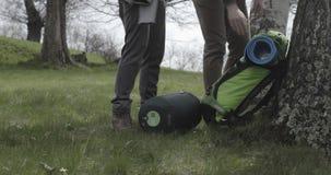Человек и женщина получая укладывают рюкзак около места располагаясь лагерем шатра в лесе березовых древесин следовать позади Люд сток-видео