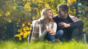 Человек и женщина предусматриванные в шотландке сидя в чае парка падения, говорить и выпивать стоковые изображения