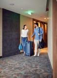 Человек и женщина приезжая на лобби гостиницы с чемоданом стоковые изображения rf