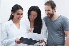Человек и женщина пришли увидеть дантиста они были встречаны работник службы рисепшн, он показывают им информацию на форме Стоковое Фото