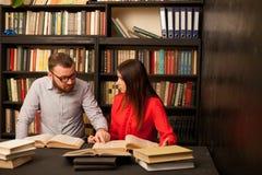 Человек и женщина прочитали книги в библиотеке подготавливают для экзамена стоковая фотография rf