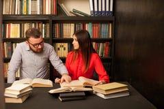 Человек и женщина прочитали много книги в библиотеке Стоковые Изображения RF