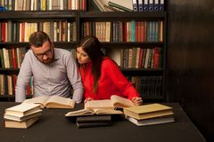 Человек и женщина прочитали много книги в библиотеке Стоковое фото RF
