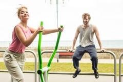 Человек и женщина работая на эллиптическом тренере Стоковые Фото