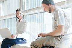Человек и женщина работая совместно в офисе просторной квартиры с компьтер-книжками Стоковое фото RF