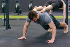 Человек и женщина разрабатывая совместно в спортзале Стоковые Изображения