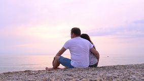 Человек и женщина сидят на пляже моря на заходе солнца акции видеоматериалы