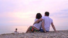 Человек и женщина сидят на пляже моря на заходе солнца сток-видео