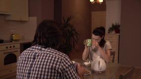 Человек и женщина сидят на таблице и обедающем иметь Она выпивает от ggreen чашка и взгляды на супруге Он ест здравицы и смотрит акции видеоматериалы