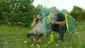 Человек и женщина сидят около чая шатра выпивая и варят shish kebab на гриле сток-видео
