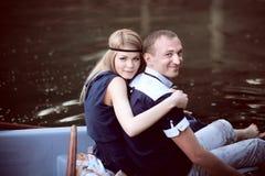 Человек и женщина сидя на краю шлюпки Стоковые Изображения RF