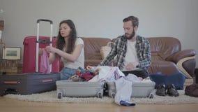 Человек и женщина сидя на поле и пакуя их ткань к большим чемоданам Концепция подготовки в дорогу видеоматериал