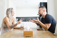 Человек и женщина сидя таблицей на противоположной стороне и споря проблемы стоковая фотография