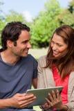 Человек и женщина смотрят в каждые другие eyes пока они владение Стоковые Изображения RF
