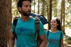 Человек и женщина смотря вокруг пока идущ вдоль пути тропы в древесинах леса Группа в составе лето людей друзей стоковые фото