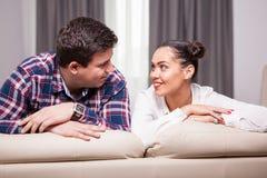 Человек и женщина смотря один другого лежа на задней части cou Стоковые Фотографии RF