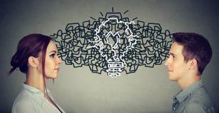 Человек и женщина смотря один другого обменивая их мысли приходя вверх вместе с электрической лампочкой идеи Стоковые Изображения