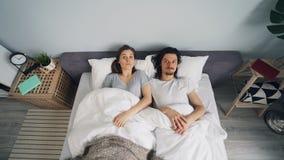 Человек и женщина спать в кровати после этого просыпая вверх и спеша от спальни акции видеоматериалы