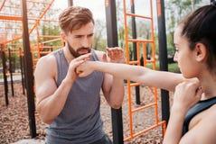 Человек и женщина стоят снаружи в парке и работать Девушка кладет в коробку пока ее тренер помогает ей Оба из  Стоковое Фото