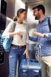 Человек и женщина с багажом стоя в современном лифте стоковые фото