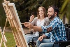Человек и женщина с invalids в кресло-колясках рисуют совместно изображение в парке Стоковые Фото