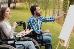 Человек и женщина с invalids в кресло-колясках рисуют совместно изображение в парке Стоковое Фото