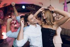 Человек и женщина танцуют на переднем плане За ими они танцуют и поют их друзья Стоковое фото RF