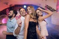 Человек и женщина танцуют на переднем плане За ими они танцуют и поют их друзья Стоковое Фото