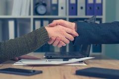 Человек и женщина тряся руки над деловым соглашением Стоковые Изображения