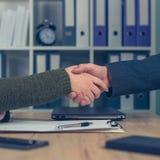 Человек и женщина тряся руки над деловым соглашением Стоковое фото RF