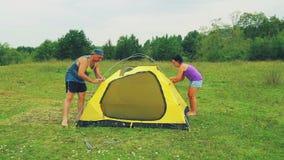 Человек и женщина установили шатер с помощью сводам для закрепления видеоматериал