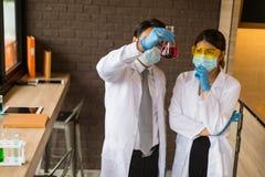 Человек и женщина ученого держа и смотря стеклянную пробирку Химик рассматривает химическую пробирку, науку, доктора Стоковое Изображение RF