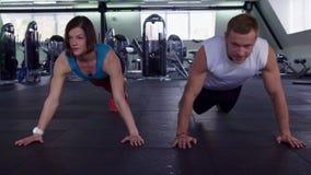 Человек и женщина фитнеса нажимают поднимают на спортзале стоковое фото